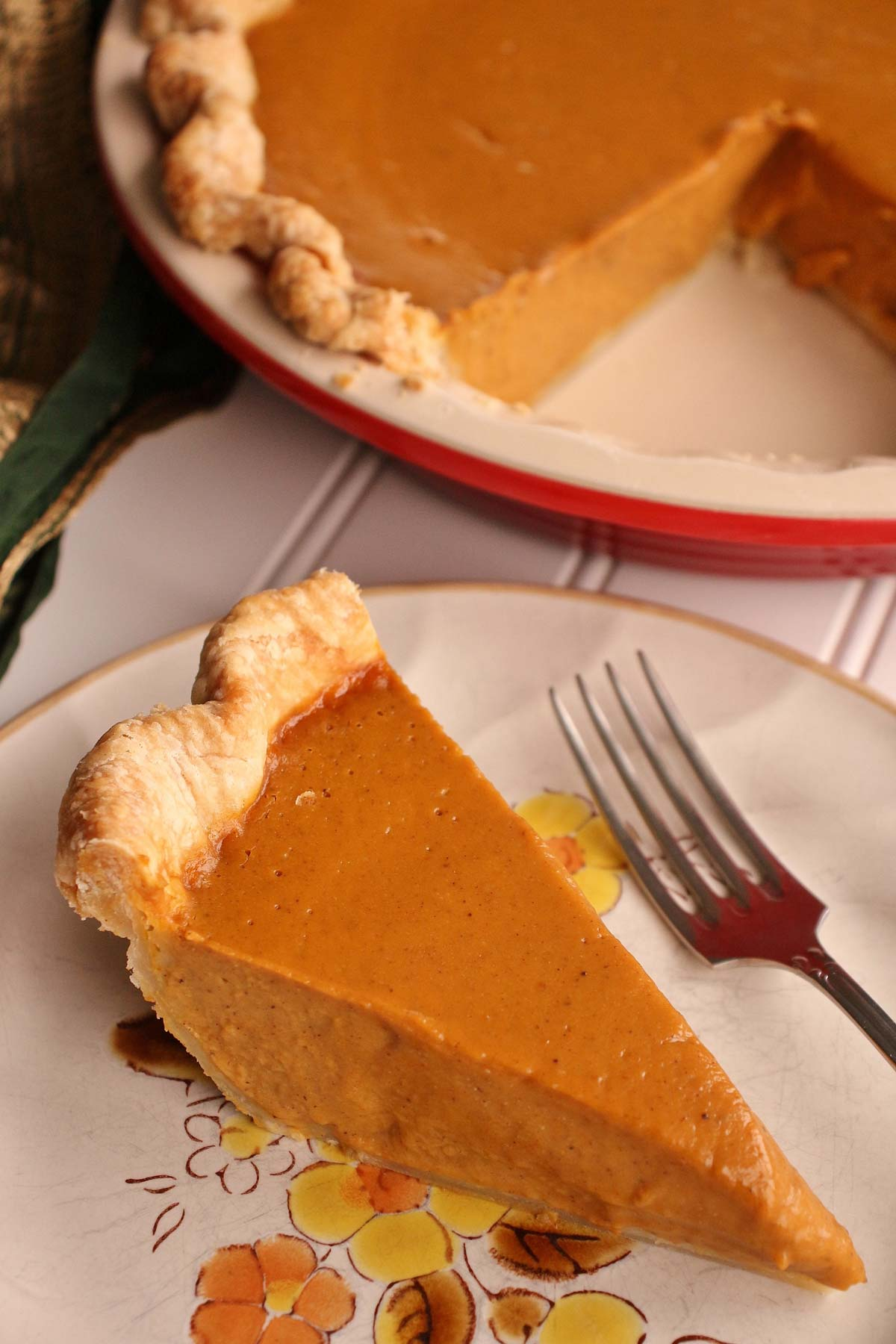 A slice of pumpkin pie on a plate with a red ceramic pie dish in the background.