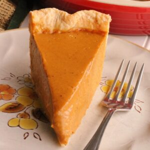 A slice of brown butter pumpkin pie on a plate with a fork next to it.