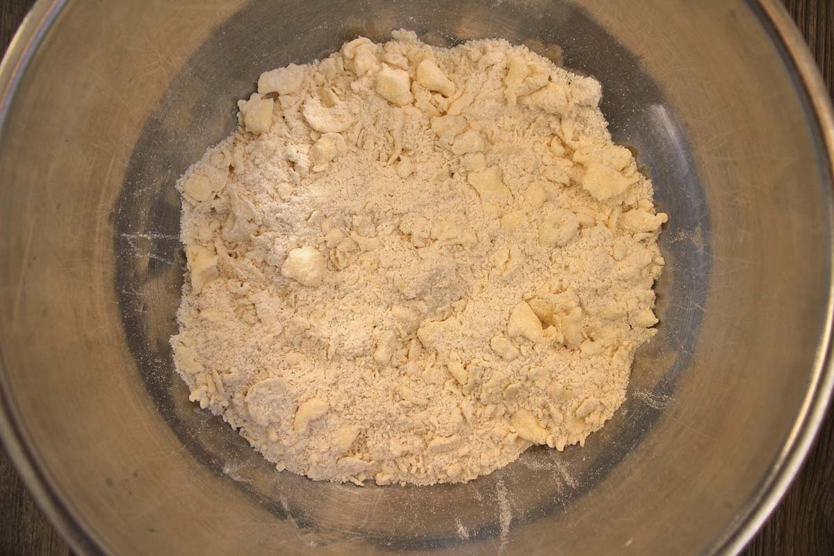 A mixture of flour with small bits of pea-sized butter in a metal mixing bowl.