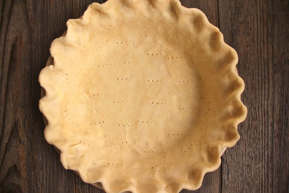 An unbaked pie crust with crimped edges pricked with a fork in the bottom and sides.