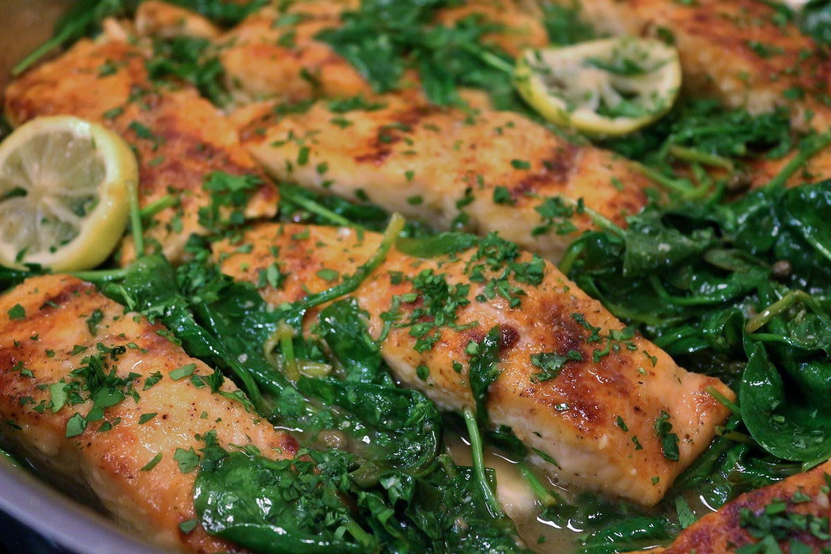 Salmon piccata fillets cooking in a pan with wilted baby spinach and lemon slices.