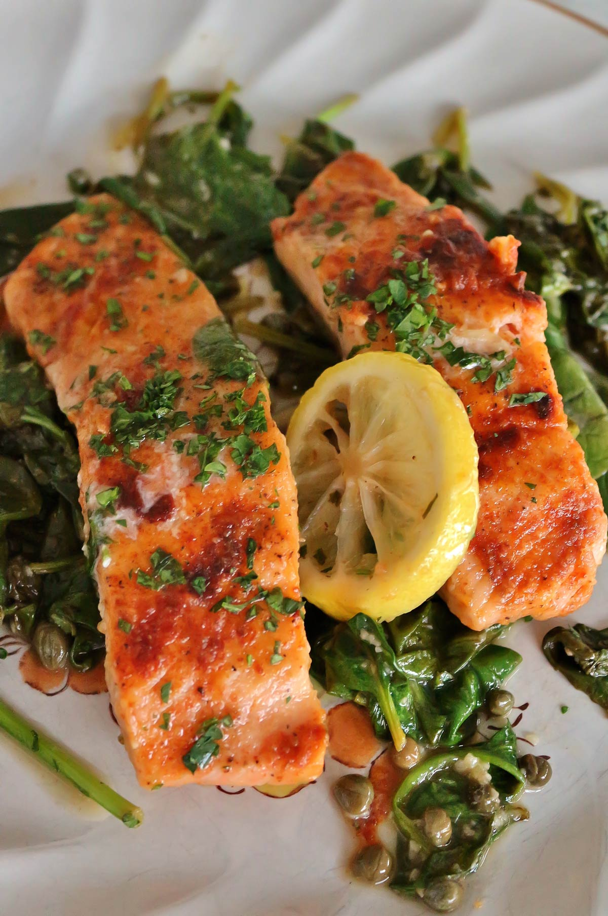 Two salmon piccata fillets with wilted baby spinach, capers and lemon slices on a rustic plate.