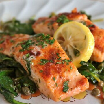 A plate of cooked salmon fillets with wilted spinach, capers and lemon slices.