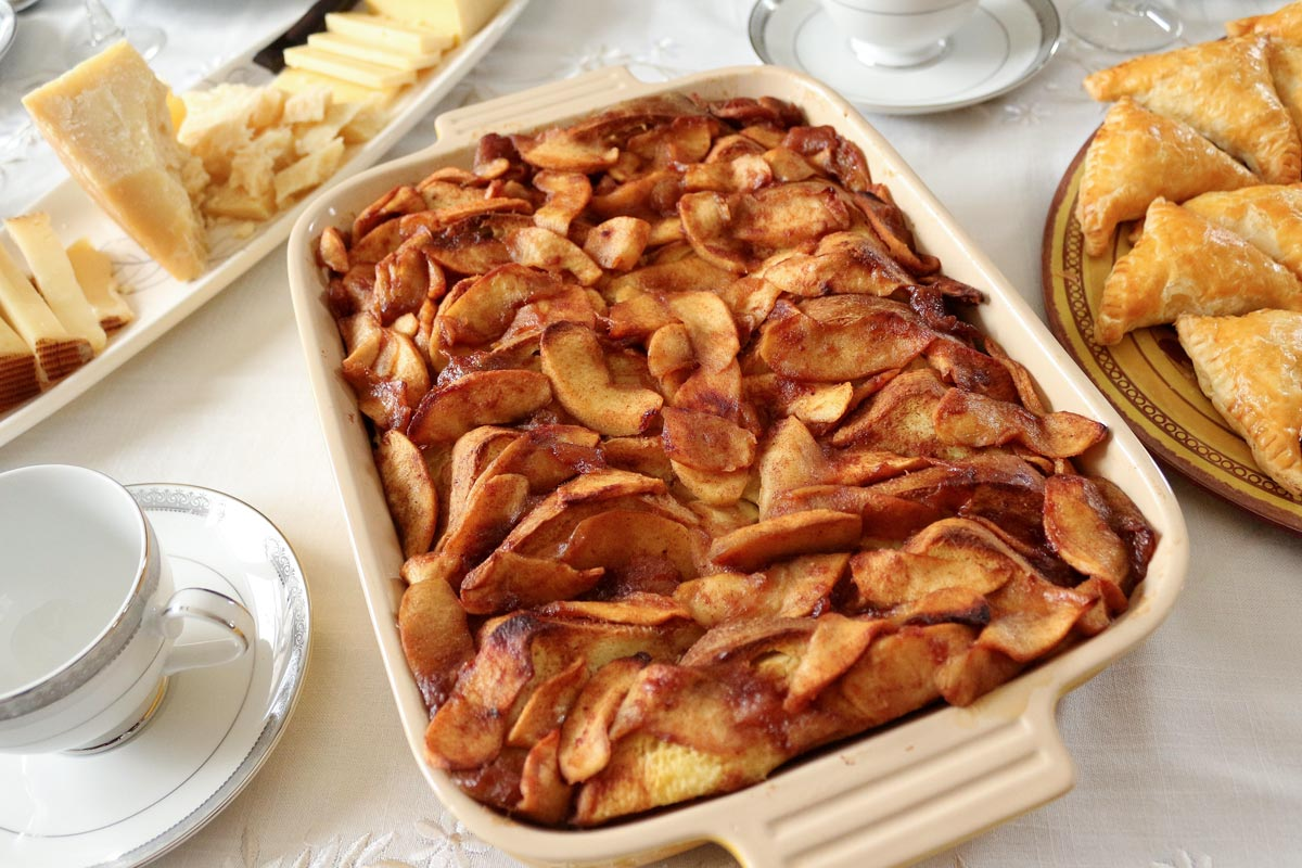 Baked apple french toast casserole on a table with teacups and a cheese platter.