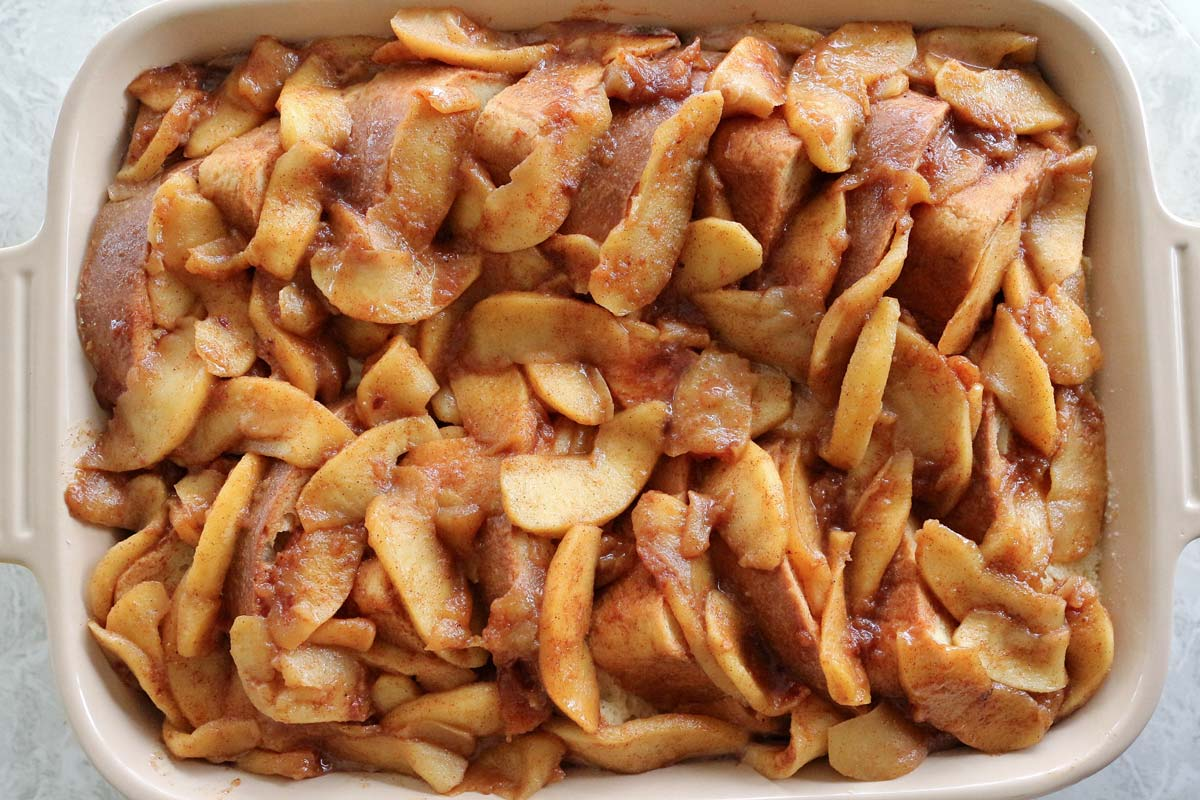 French toast casserole with apples in a rectangular dish before baking.