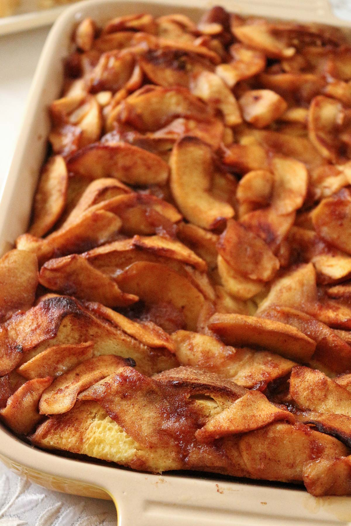 Closeup of baked apple french toast in a ceramic baking dish.