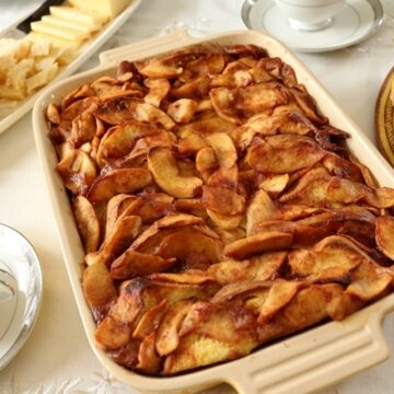 Baked cinnamon apple french toast in a casserole dish next to a cheese board and turnovers