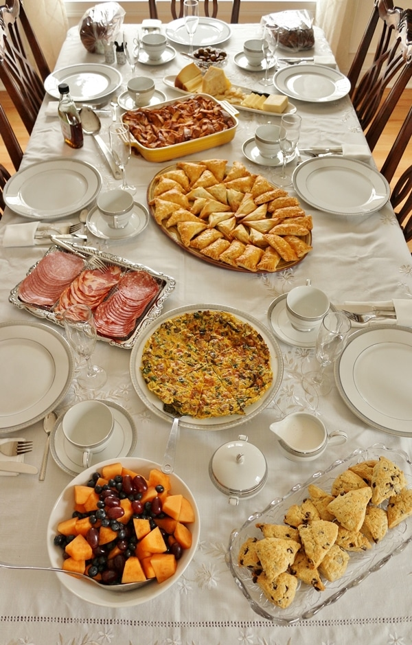 Table set for brunch with a cheese platter, baked french toast, cold cuts, scones, and fruit
