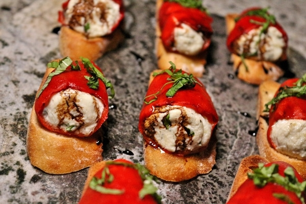 Stuffed piquillo peppers with goat cheese on sliced baguettes with balsamic glaze and basil on a granite serving dish