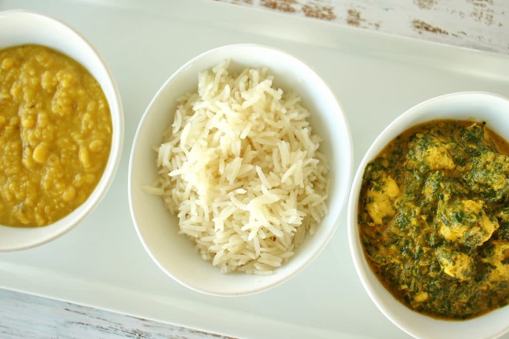 A row of 3 small white bowls. From left to right, they are filled with chana dal (a golden colored Indian lentil dish), basmati rice, and chicken saag (spinach curry).