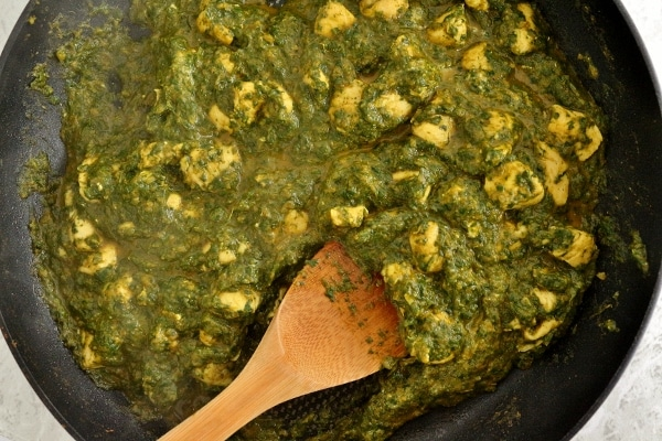 Chicken saag in a skillet with a wooden spoon