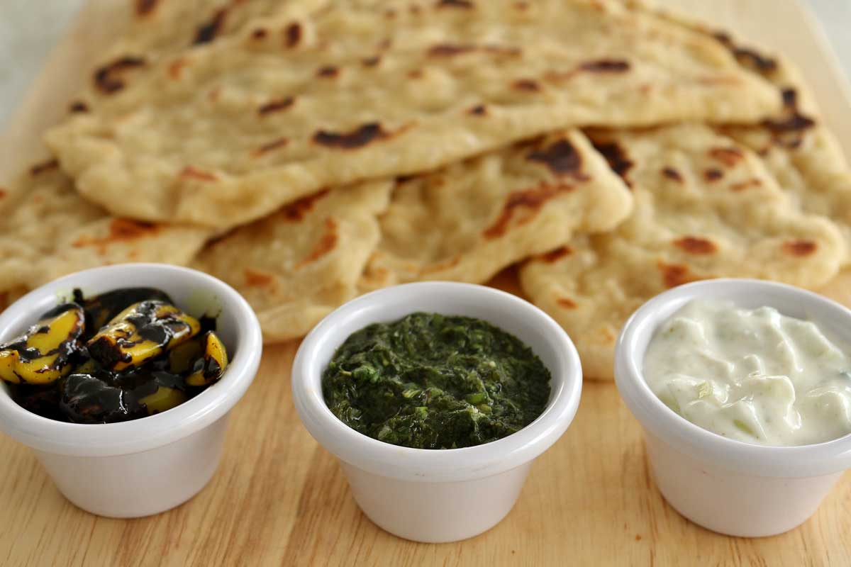 Three dipping sauces in little cups with a pile of naan in the background.