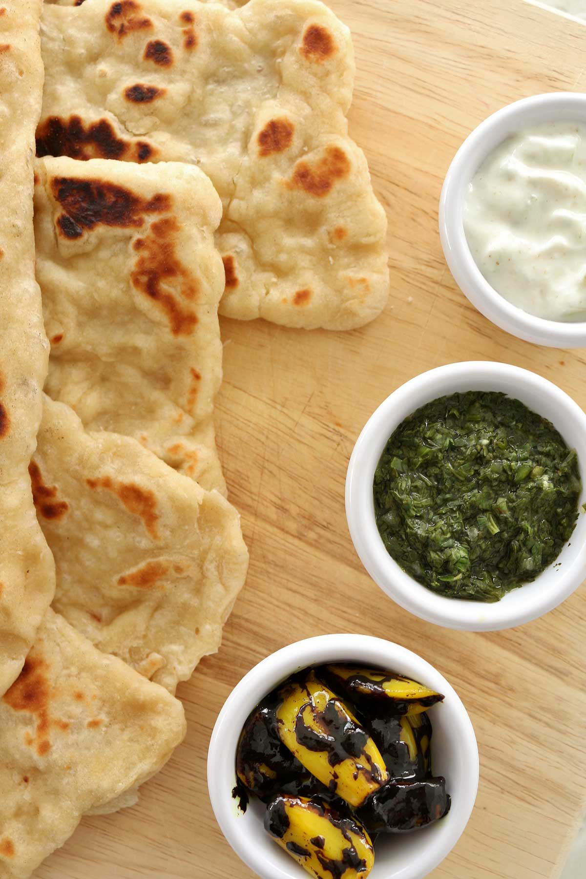 A close up 3 small cups filled with Sanaa dipping sauces next to naan bread.