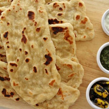 A pile of naan on a wooden board next to 3 cups of dipping sauces.