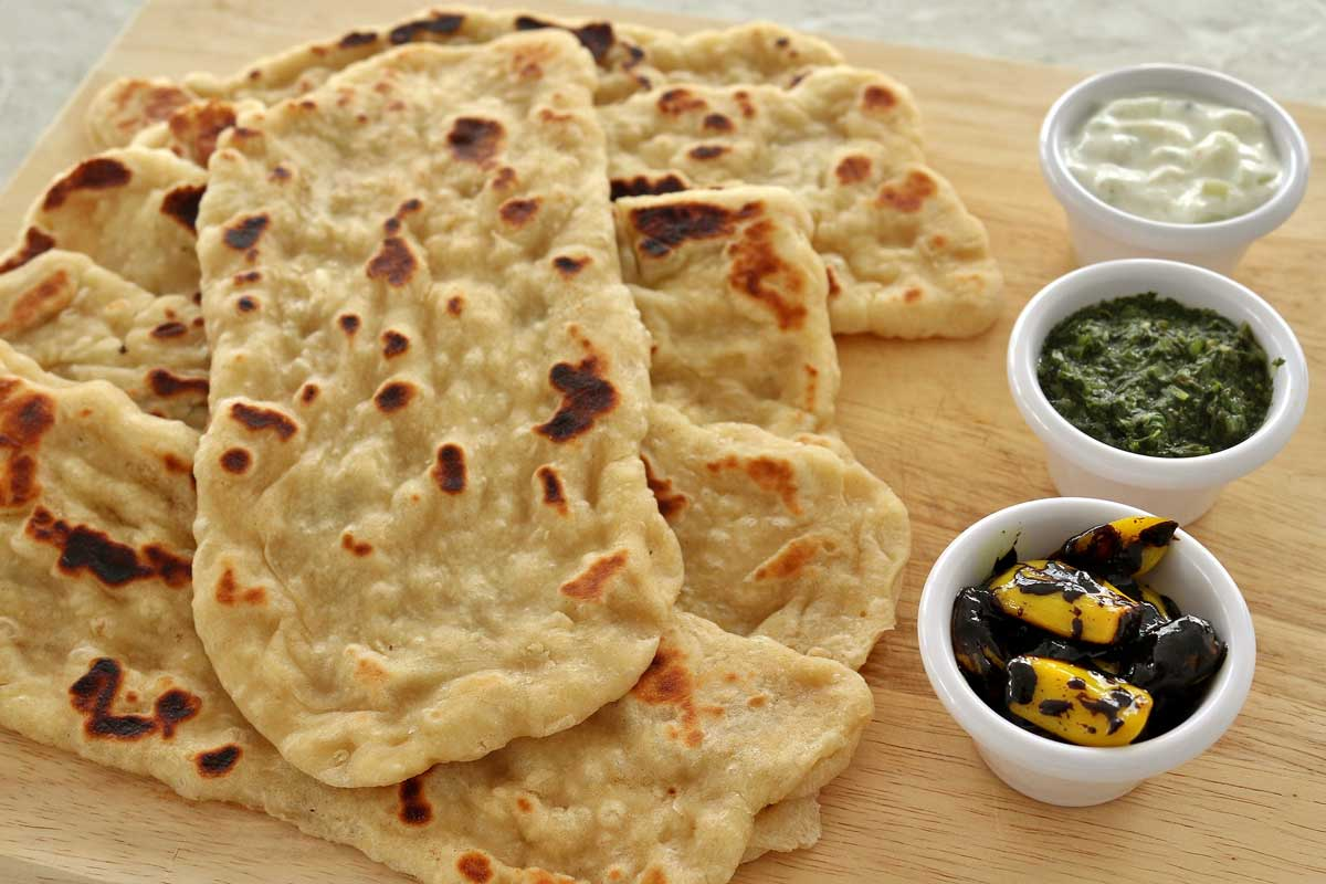 A pile of naan on a wooden board with 3 dipping sauces on one side.