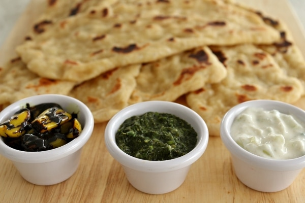 Three Sanaa dipping sauces in little cups on a wooden board with a pile of naan in the background