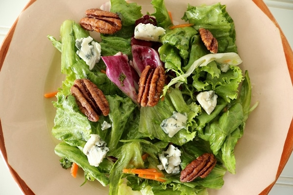 A plate of salad with pecans and blue cheese