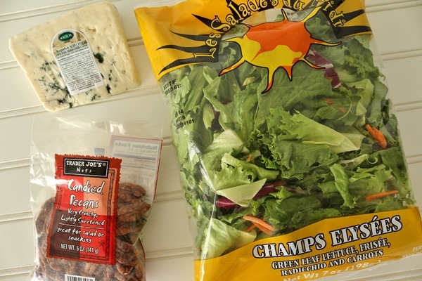 a bag of salad greens, pecans, and wedge of blue cheese