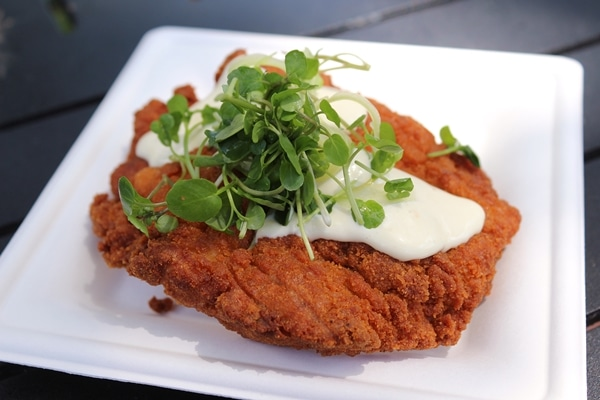a fried piece of chicken topped with sauce and greens