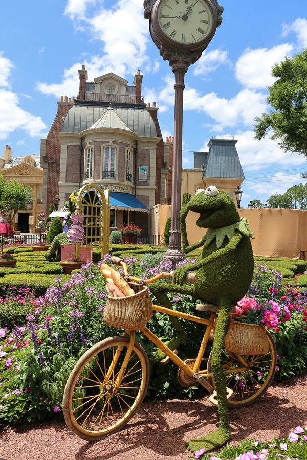 a topiary shaped like Kermit riding a bicycle