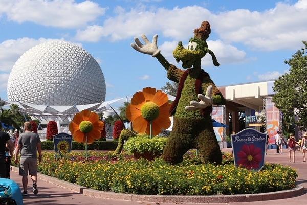 a topiary shaped like Goofy with Spaceship Earth in the background