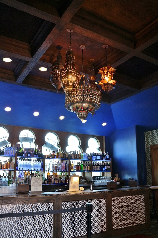 restaurant bar with bright blue walls and gold chandelier