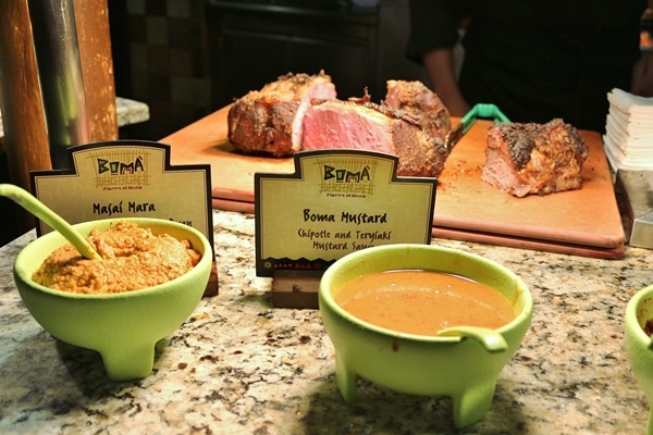 2 bowls of sauce in front of a cutting board topped with roast beef