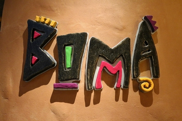 a colorful wall sign that says Boma