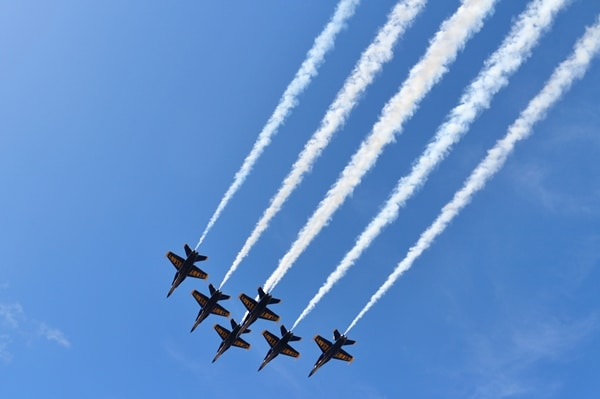 A group of fighter jets flying through a blue sky