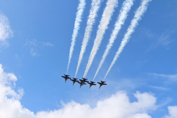 the Blue Angels fighter jets flying through a cloudy blue sky