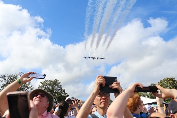 fighter jets flying over a group of people
