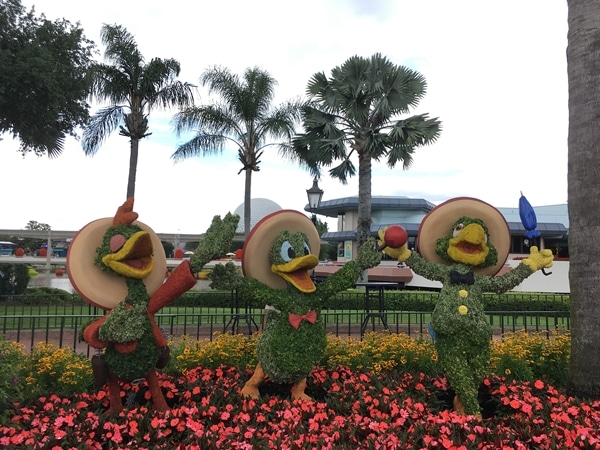a topiary display of The Three Caballeros with palm trees behind them