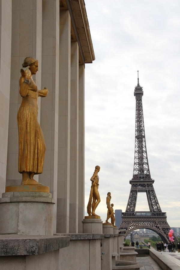 a row of gold statues in front of the Eiffel Tower