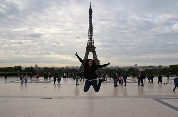 a woman jumping in front of the Eiffel Tower