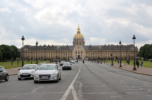 Les Invalides building with its gold dome at the end of a busy street