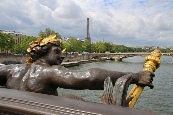 A statue of a man with the Eiffel Tower in the distance