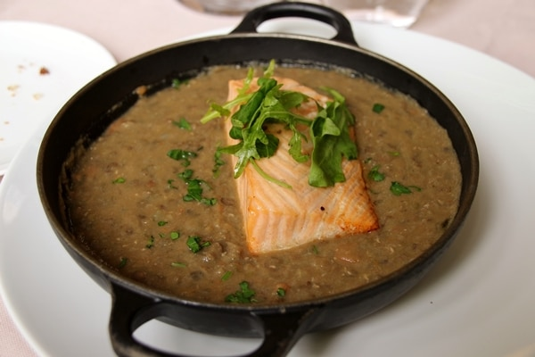 a wide pan of lentils topped with a fillet of salmon
