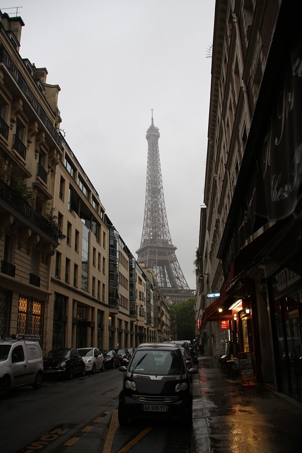 a rainy city street with the Eiffel Tower in the distance