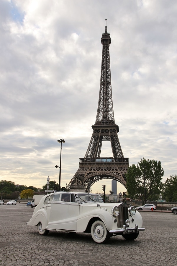 a white antique car in front of the Eiffel Tower