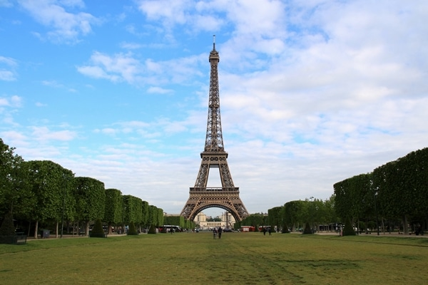 the Eiffel Tower at the end of a large grassy field