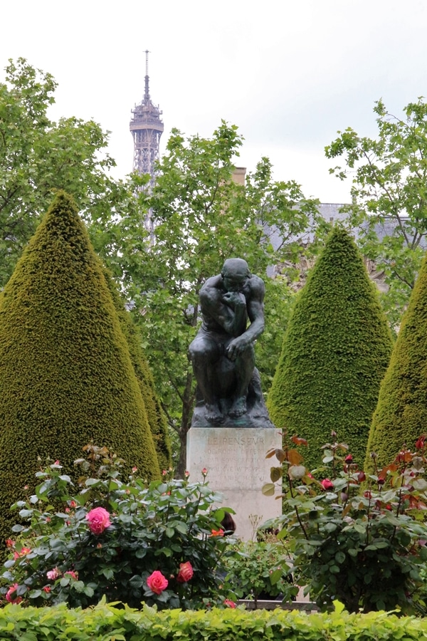The Thinker sculpture in a flower garden
