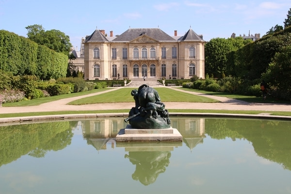 a sculpture in a pond in front of a grand building