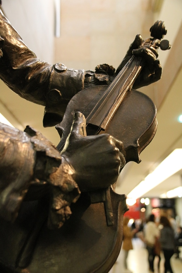 closeup of a statue of hands holding a violin