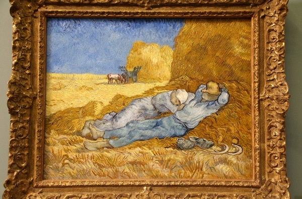 A painting of 2 people on a pile of hay