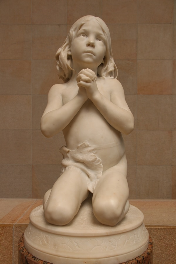 a sculpture of a young boy praying