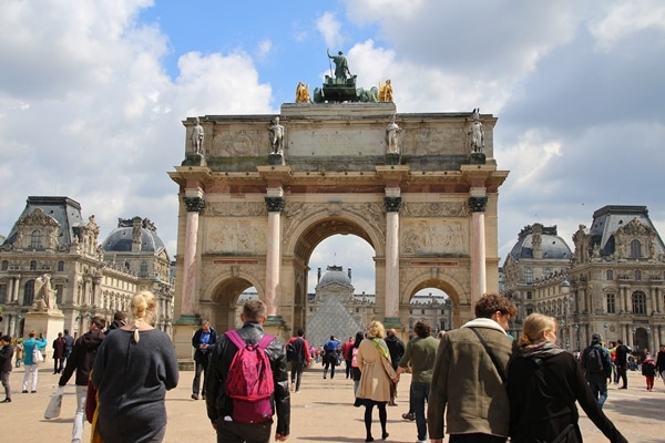 A group of people walking in front of Arc de Triomphe du Carrousel