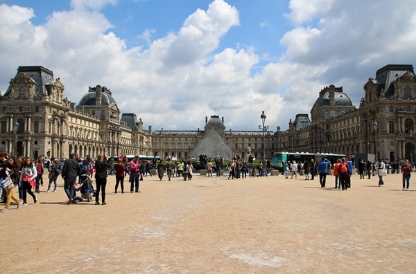 A group of people in front of the Louvre