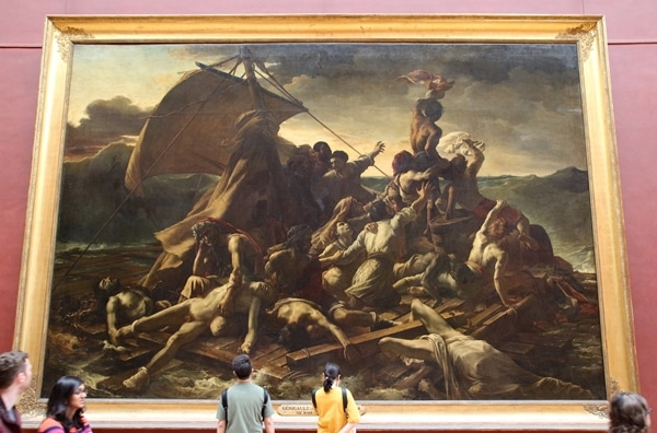 A group of people standing in front of a large painting