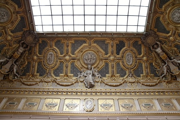 a gilded ceiling with sculptures and a skylight