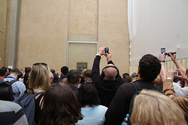 A group of people standing in front of the Mona Lisa taking photos